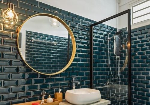 a-stylish-bathroom-clad-with-teal-tiles-with-a-midnight-blue-vanity-gold-fixtures-and-a-gold-frame-mirror